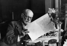 Sigmund Freud mentre corregge alcuni suoi scritti al tavolo da lavoro