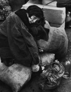 Little girl resting during the evacuation of the city di Robert Capa