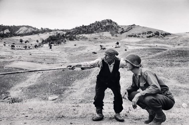 Sicilian peasant telling an American officer which way the Germans had gone di Robert Capa