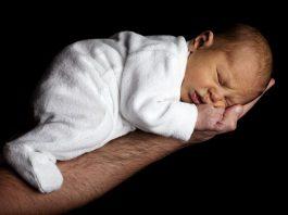 Un neonato che dorme nella mano del suo papà, una delle più belle foto di bambini neonati del nostro elenco