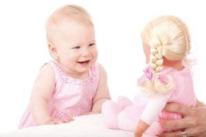 Una bambina che ride alla sua bambola