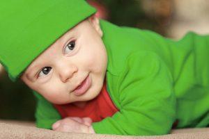 Un neonato vestito di verde