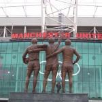 """L'ingresso dell'Old Trafford, con le statue della """"sacra trinità"""" dello United, cioè George Best, Denis Law e Bobby Charlton, esattamente di fronte alla statua del loro allenatore, sir Matt Busby"""