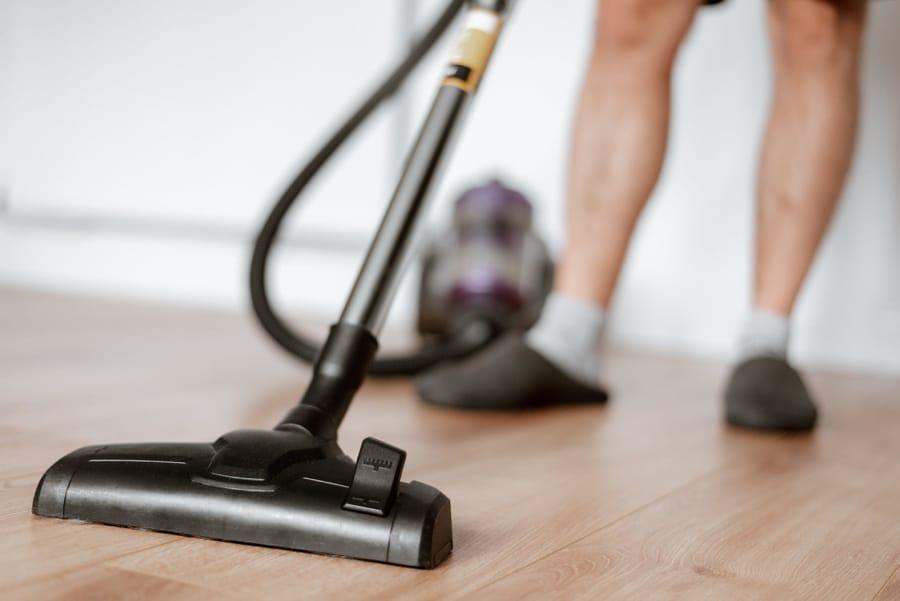 Un uomo che pulisce il pavimento, collaborando ai lavori domestici