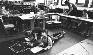 Una scuola montessoriana negli anni '70, con i ragazzi che occupano posti diversi e portano avanti attività diverse