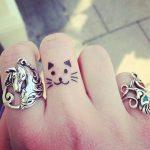 Un gattino sorridente tatuato su un dito medio