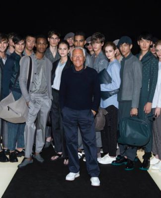 Giorgio Armani, uno degli stilisti italiani più famosi nel mondo, circondato dai suoi modelli