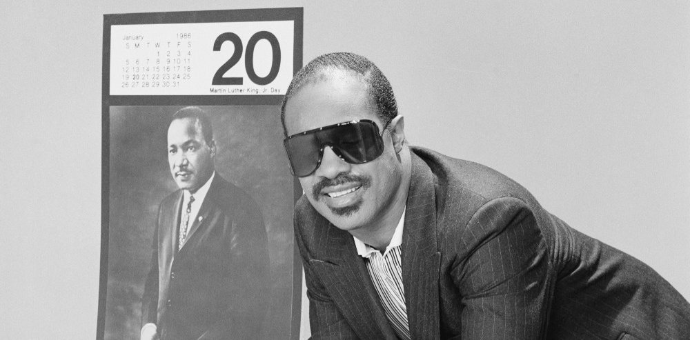 Stevie Wonder davanti a un manifesto per l'istituzione del Martin Luther King Day