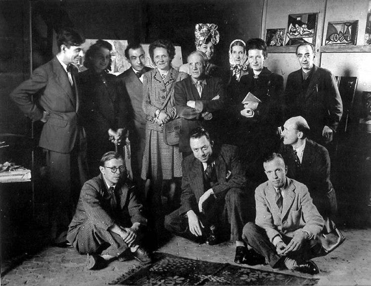 Filosofi ed artisti nell'atelier di Picasso nel 1944. Sono riconoscibili, in piedi Jacques Lacan (il primo a sinistra), Pablo Picasso (al centro), Simone de Beauvoir (prima donna da destra) e, seduti, Jean-Paul Sartre (il primo a sinistra) e Albert Camus (il secondo)