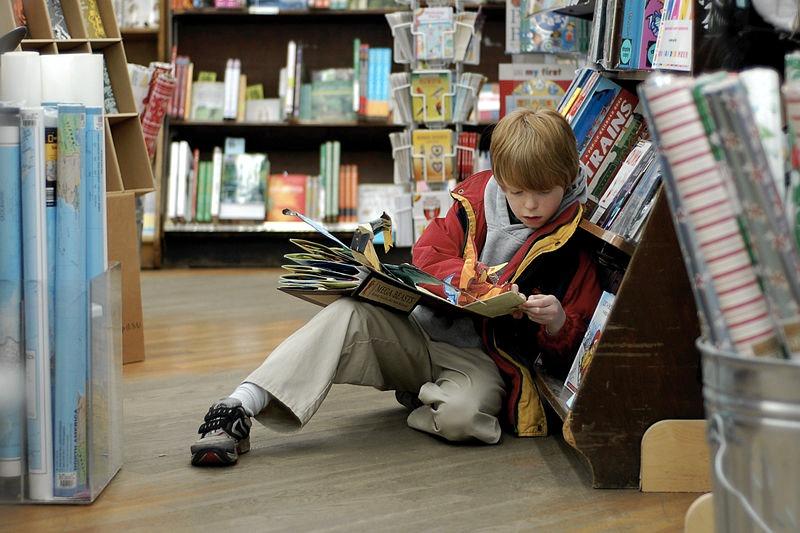 Un bambino legge un libro pop-up in una libreria (foto di Tim Pierce via Flickr)