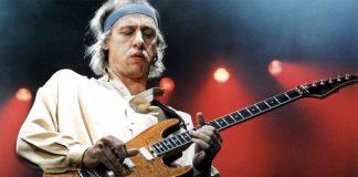 Mark Knopfler col suo caratteristico modo di suonare la chitarra