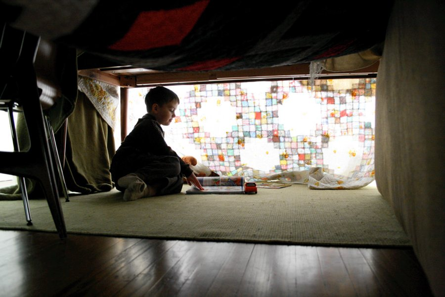 Un bambino in un fortino improvvisato (foto di Ben Husmann via Flickr)