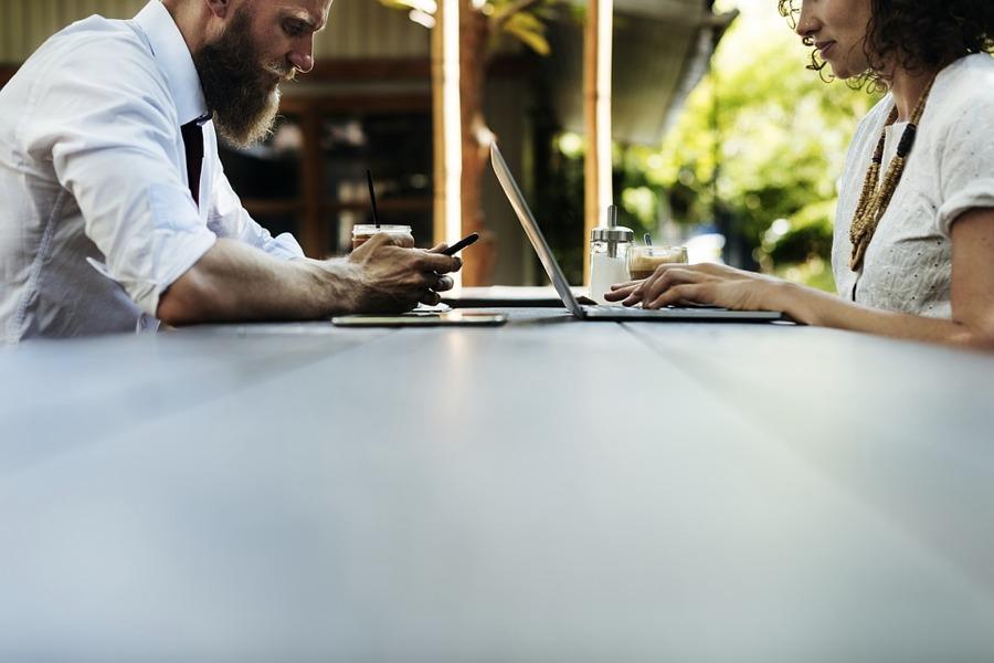 Uomo e donna a un tavolo, ma che non si guardano