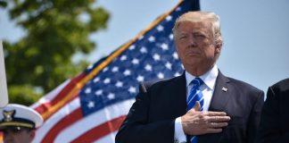 Donald Trump con la bandiera statunitense alle spalle