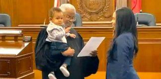 Juliana Lamar presta giuramento da avvocata davanti a un giudice che tiene in braccio suo figlio