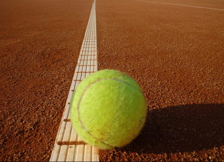 Una pallina da tennis sulla linea del campo